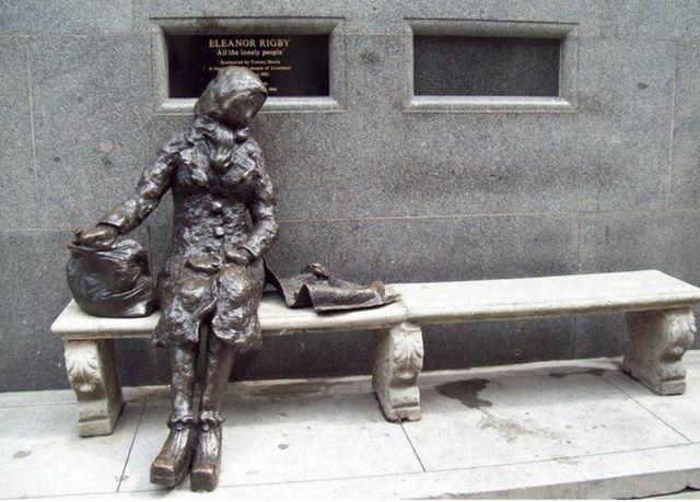 Escultura de Eleanor Rigby em bronze, sentada em um banco de pedra