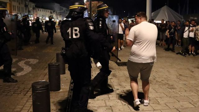 An England football fan scuffles with a police officer in Marseille