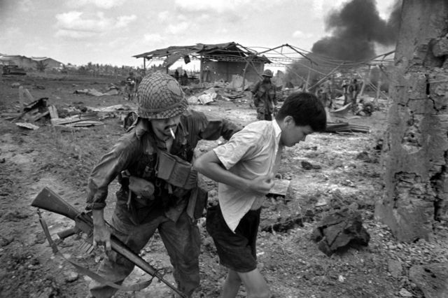 An American soldier forcefully pushes a Vietnamese person in a scene of devastation