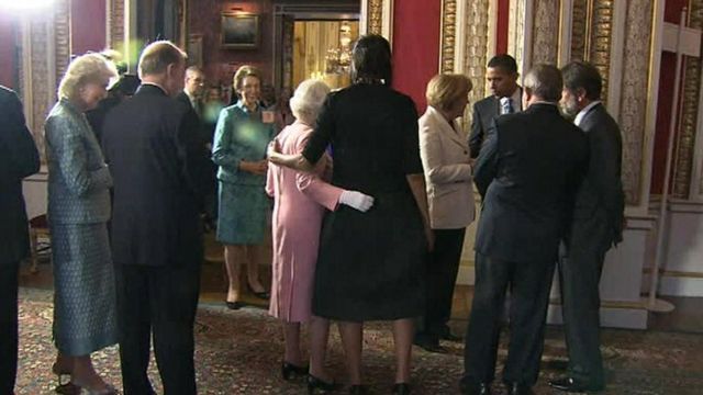 the queen places her arm around Michelle Obama in 2009