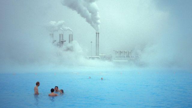 Planta geotérmica y gente en baños termales.