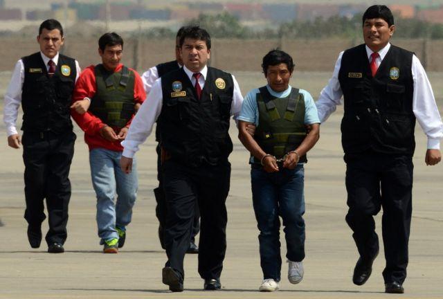 """Alexander Alarcon, alias el """"Camarada Renán"""" (izquierda), y Dionisio Ramos, alias """"Camarada Yuri"""", miembros de la guerrilla maoista Sendero Luminoso, escoltados por la policía a su llegada a Lima tras ser detenidos en la región amazónica de Junín el 10 de agosto de 2015."""
