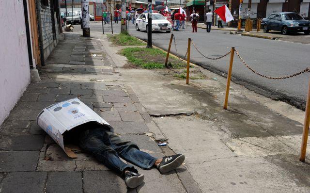 Vagabundo duerme en la calle metido en una caja de cartón en San José, Costa Rica, el 29 de abril de 2010.