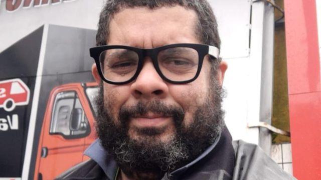 Jucelio, um homem de óculos, barba e olhar triste, olha para a câmera