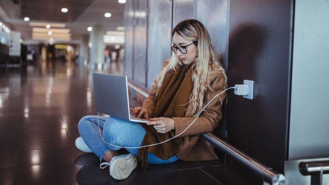Una joven sentada en el suelo con una laptop enchufada
