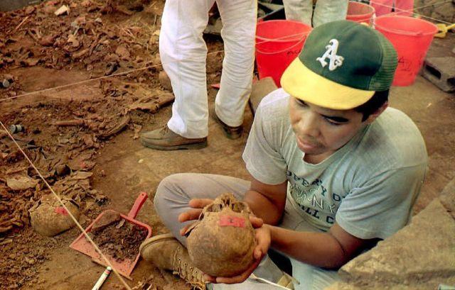 Hombre sostiene un cráneo extraído de El Mozote en 1992.