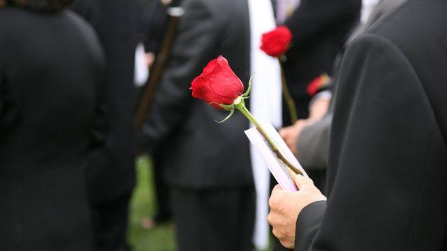 Pessoas com roupas pretas em pé em funeral, algumas segurando rosas