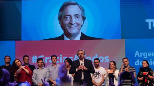 Alberto Fernández (centro) con una imagen de Néstor Kirchner detrás
