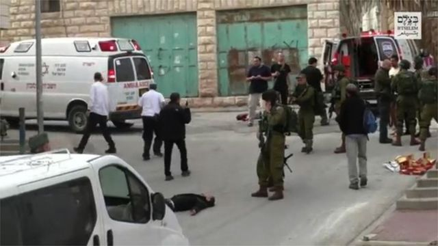 A scene from the video showing Sgt Azaria raising his rifle at the wounded Palestinian