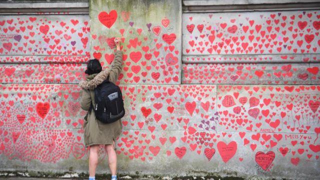 Londra'daki Embankment'teki Ulusal Covid Anıt Duvarı'na bir kişi kalbinde yazıyor