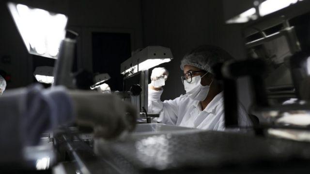 Un investigador con mascarilla observando frascos de dosis de fármacos.
