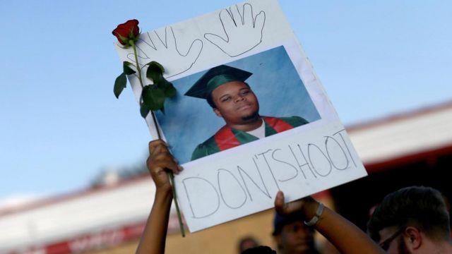 一位游行示威者举着迈克尔·布朗(Michael Brown)的照片,照片上的这个18岁男孩于2014年在美国密苏里州弗格森(Ferguson, Missouri)在未携带武器的情况下遭一名警察开枪杀死。
