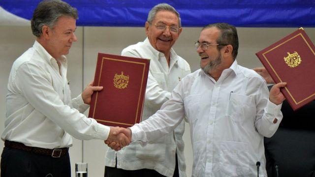 Juan Manuel Santos estrecha la mano de Timochenko mientras Raúl Castro sonríe.