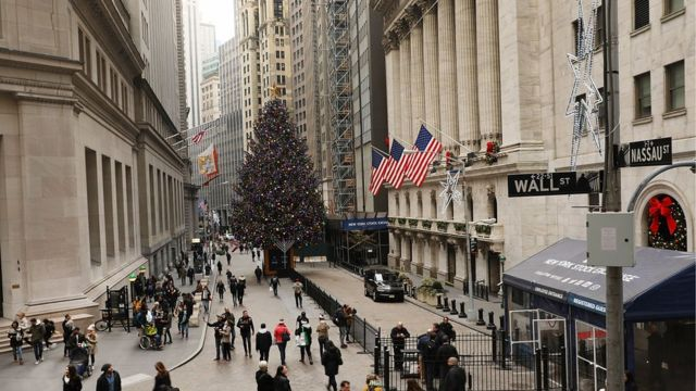 People walk in front of the New York Stock Exchange
