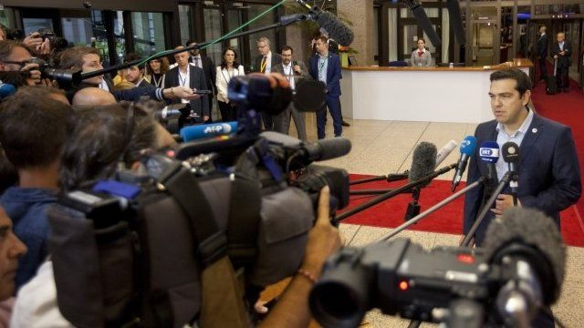 Greek Prime Minister Alexis Tsipras, right, speaks with the media as he leaves after a meeting of eurozone heads of state at the EU Council building in Brussels on Monday, July 13, 2015.