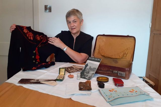 Judith Rhodes with her mother's suitcase and some of the belongings she brought with her