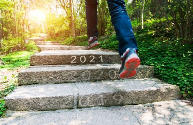 Un joven subre escalones con los años 2019, 2020 y 2019