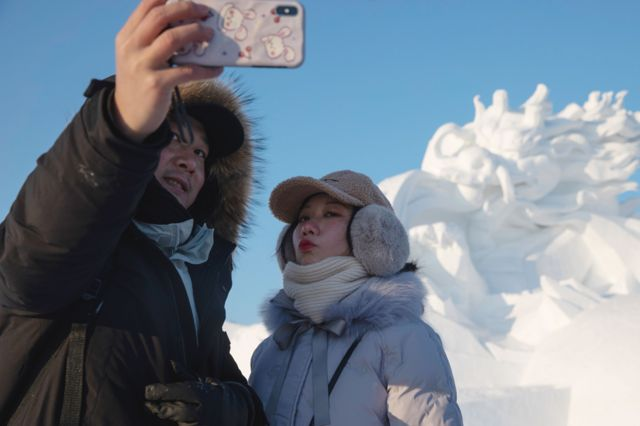 Two people take selfie in front of a snow sculpture