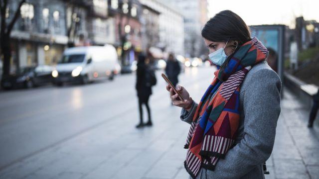 Mujer con mascarilla y celular
