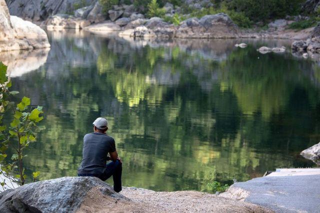 """সেপ্টেম্বর: """"ভার্জিনিয়ার গ্রেট ফলস্ ন্যাশনাল পার্কে পটোম্যাক নদীর কূলে পাথরের ওপর বসে জিরিয়ে নিচ্ছেন প্রেসিডেন্ট ওবামা।"""""""