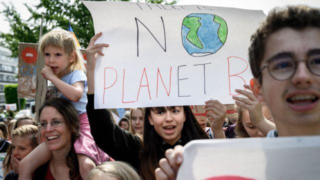 """Padres y niños con una pancarta que reza: """"no hay planeta B"""""""