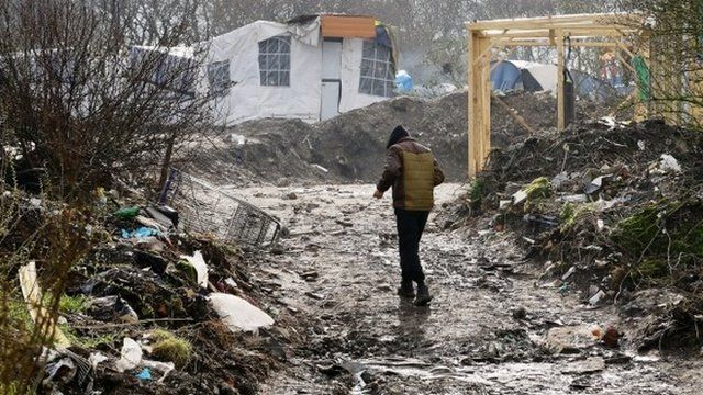 A man walks through the Jungle migrant camp in Calais, France