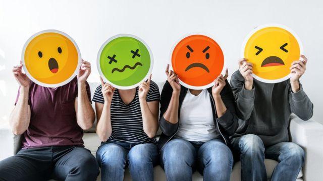 Personas con dibujos de caras con sentimientos negativos.