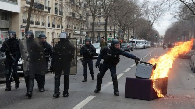 A member of the riot police removes a garbage bin from a fire started by demonstrators protesting against alleged police brutality in Paris (23 February 2017)