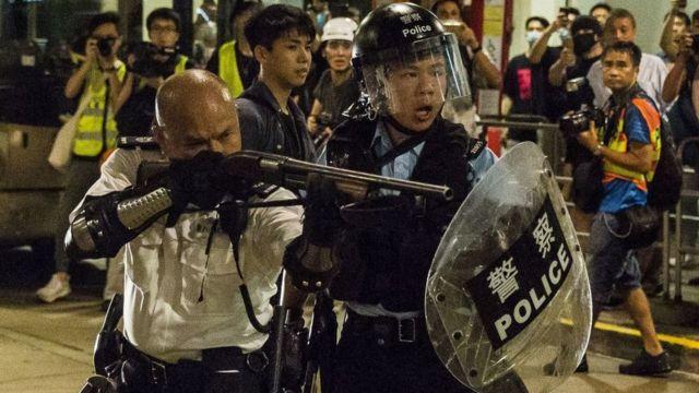 香港新界葵涌警署外一名警署警长(左)举起雷鸣登霰弹枪指向示威者(30/7/2019)