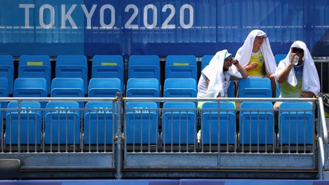 Entrenadores se protegen del calor en el estadio Ariake de tenis en Tokyo 2020