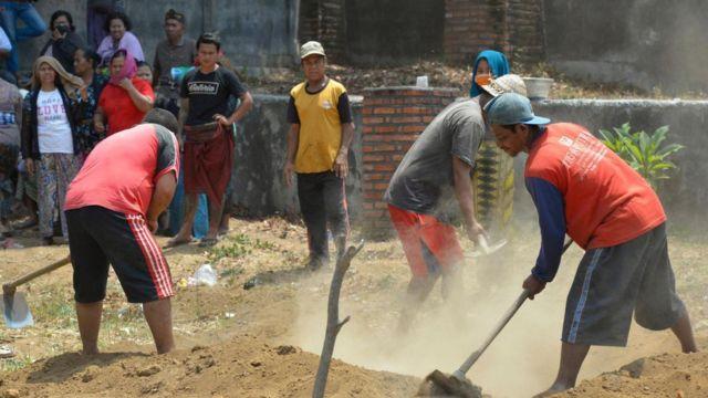 Imagem mostra homens cavando túmulo em aldeia na Indonésia