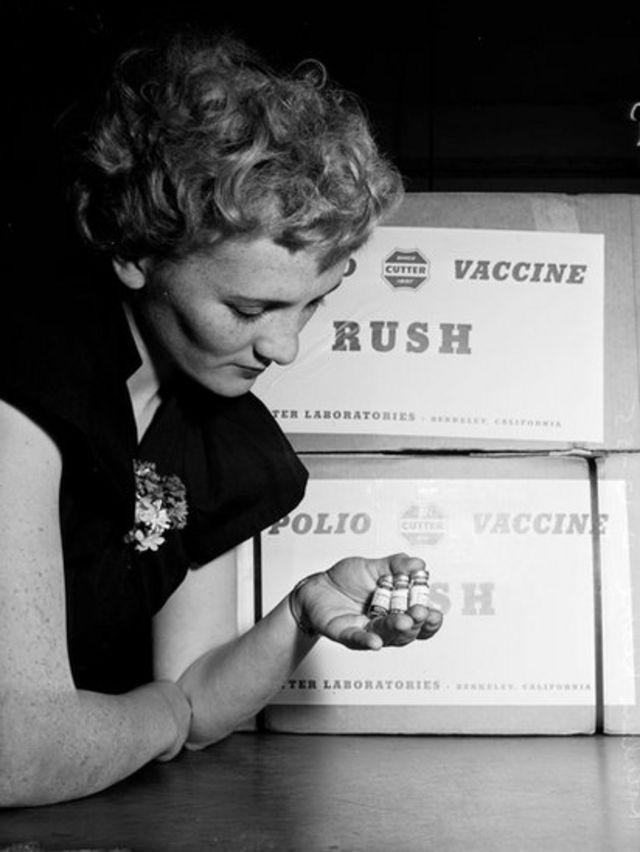 Una mujer sosteniendo frascos de la vacuna contra la polio de los laboratorios Cutter.