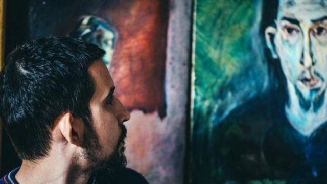 Homem olhando para rosto de outro homem em um quadro