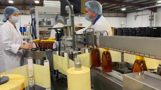 Workers filling bottles with honey
