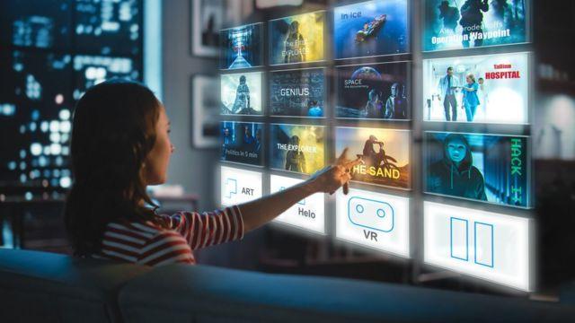 Una mujer selecciona programas en una pantalla virtual de TV