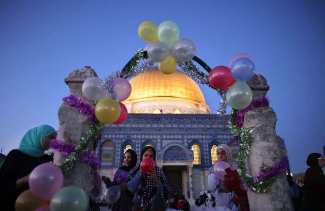 طفلات فلسطينيات ينفخن البالونات في ساحة المسجد فجر الخميس