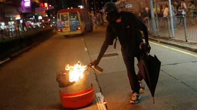 Un manifestante prende fuego a un cesto de la basura.