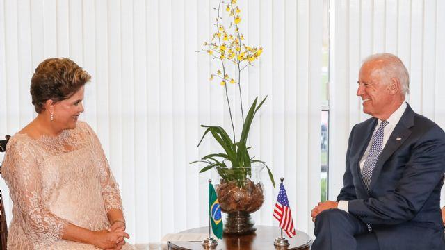 Dilma e Biden sorriem um para o outro, sentados em sala