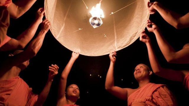 Monjes budistas lanzan una linterna durante el festival Yee Peng en Chiang Mai.