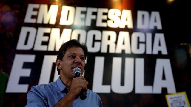 """Fernando Haddad ao microfone; ao fundo, lê-se """"Em defesa da democracia e de Lula"""""""