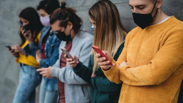 Pessoas de máscara no celular