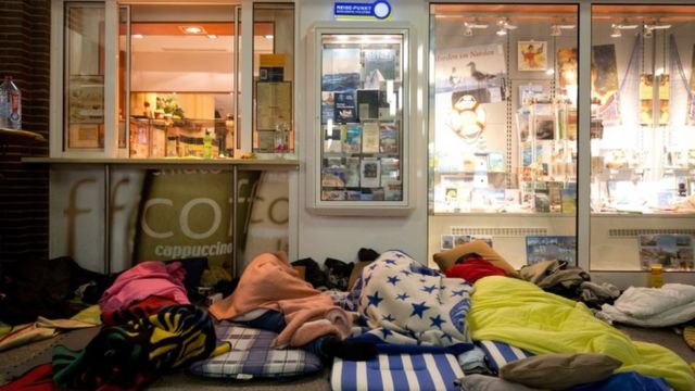 Immigrants sleep in a train station in Germany on their route to seek asylum in Denmark. 015