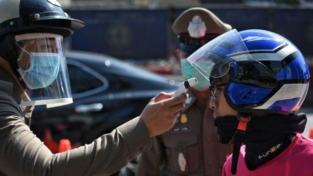 Một thành viên Cảnh sát Hoàng gia Thái Lan đo nhiệt độ của một người lái xe giao thức ăn trong biện pháp phòng ngừa chống lại sự lây lan của virus corona tại một trạm kiểm soát ở ngoại ô Bangkok