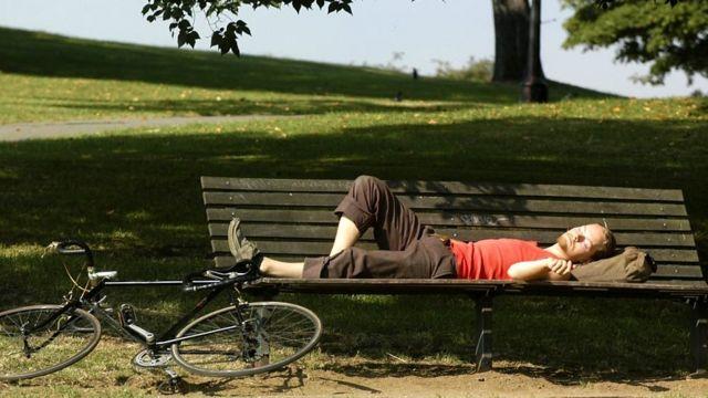 ผู้ชายนอนหลับบนม้านั่งในสวนสาธารณะ