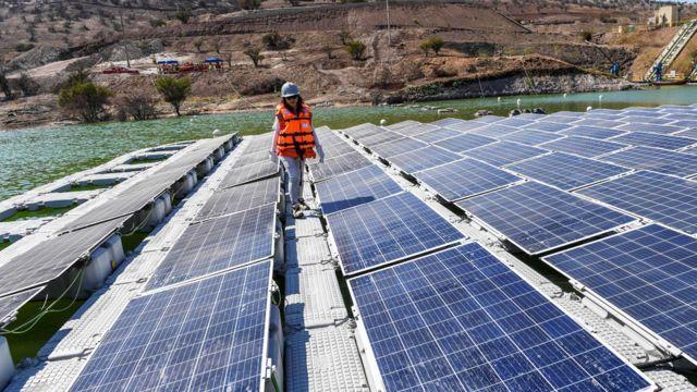 Mujere caminando entre paneles solares