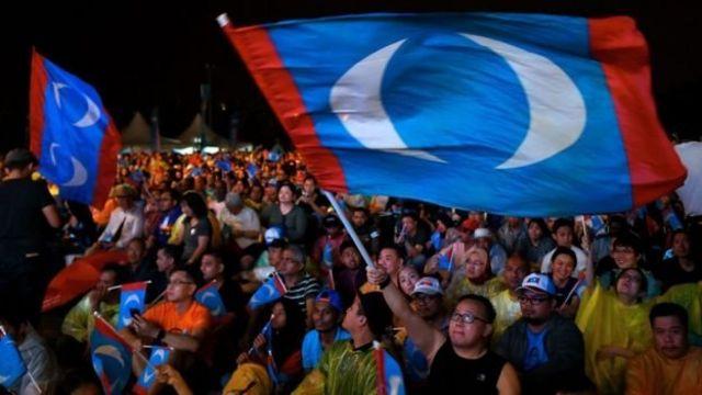 Pakatan Harapan destekçileri bayraklarla kutlama yapıyor.