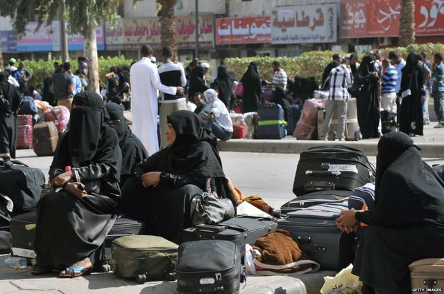 Foreign workers wait with their belongings before boarding police buses in Riyadh (file photo)