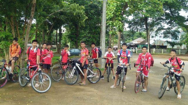 Meninos tailandeses em suas bicicletas pouco antes de entrar na caverna de onde foram resgatados