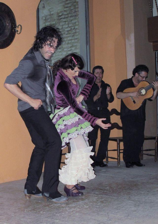 Dos bailarines de flamenco acompañados por una guitarra y un cantante