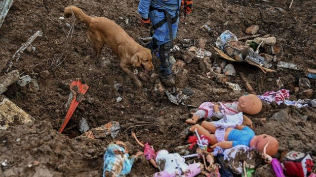 A member of the Colombian Red Cross and his dog, Gretta, search for victims amid dolls